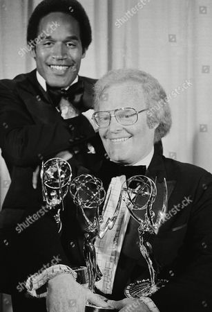 Roone Arledge, executive producer for ABC-TV sports, holds an armful of Emmys at 28th annual Emmy Awards show on Monday, Nov.18, 1976 in Los Angeles. In the background is football star O.J. Simpson