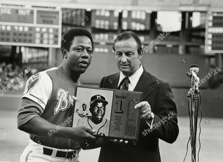 """Aaron Musial Newly crowned home-run king Hank Aaron, left, of the Atlanta Braves, is presented with a Number 1 plaque by former St. Louis Cardinals great Stan """"The Man"""" Musial in pre-game ceremonies in St. Louis, Mo., . Aaron hit his first major league home run against the Cardinals on April 23, 1954"""