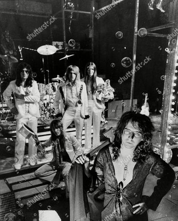 """Alice Cooper, Vincent Damon Furnier, Vincent Furnier, Michael Bruce, Neal Smith, Glen Buxton, Dennis Dunaway Glam rock star, Alice Cooper, foreground, with hatchet, poses with his band in New York, . """"It's more or less the decade of the star again"""" says Cooper. """"The old publicity stunts work."""" Such stunts include: fake hangings; decapitations; a seven-foot toothbrush; a bubble machine and a male lead singer with a female's name. The band members are, left to right: Michael Bruce; Neal Smith, sitting; Glen Buxton and Dennis Dunaway"""