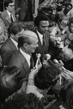 Israeli Foreign Minister Moshe Dayan, top left, and Andrew Young, former U.S. Ambassador to the United Nations, top center, hold a news conference outside the Regency Hotel on in New York. Dayan said he would welcome Young to visit his country, as long as it had nothing to do with the Palestine Liberation Organization