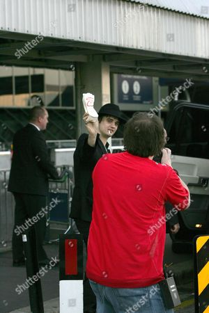 Pete Doherty pours his smoothie over photographer Carl Sims. Pete threw an Innocent smoothie over photographers as he arrived at Heathrow.