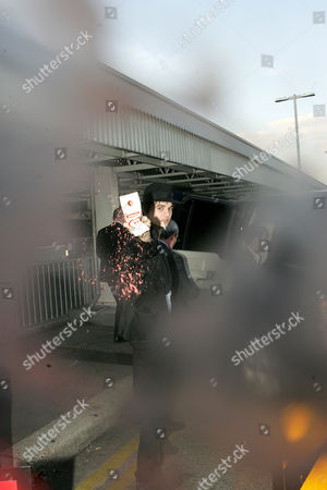 Pete Doherty pours his smoothie over photographer Carl Sims and his camera. Pete threw an Innocent smoothie over photographers as he arrived at Heathrow.