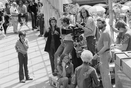 """Stock Image of Actress Audrey Hepburn, center, gestures as she confers with director Peter Bogdanovich during a scene from the movie """"They All Laughed"""", being shot on location at New York's Rockefeller Center, . Glenn Scarpelli, left, watches goings-on nearby as he passed idle time between takes"""