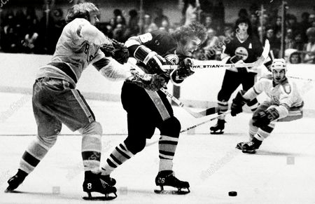 Stock Picture of Don Burgess, Mel Pearson Philadelphia Blazers Don Burgess (8) and Minnesota Fighting Saints Mel Pearson (26) fight for the puck in World Hockey Association action in Philadelphia