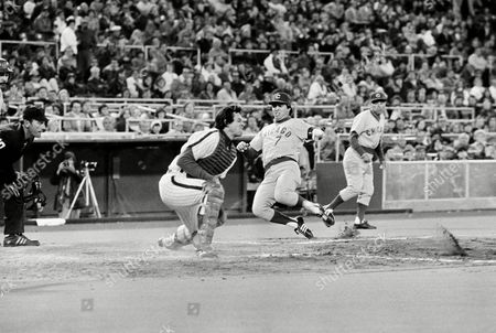 Chicago Cubs' Bobby Murcer glides past Phillies' catcher, Bob Boone, as ball raises dust behind him Monday night at game in Philadelphia, . Cubs' Jose Cardenal scored ahead of Murcer on Jerry Morales' double and Morales walked across the plate on the error throw to Boone. The three runs were scored in the 8th inning and the Cube won, 6-2