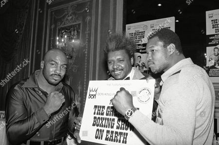 Boxing promoter Promoter Don King center holds placard proclaiming the Greatest Boxing Show on Earth as heavyweight Earnie Shavers, left, and Larry Holmes, right, pose at New York news conference on . The conference was called to announce that Shavers and Holmes will face each other in a 12-round, televised bout at Las Vegas on March 25