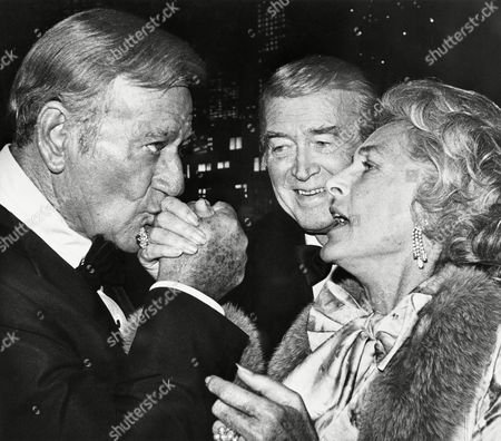 """John Wayne kisses the hand of Gloria Stewart as Jimmy Stewart looks on as they exchange greetings at an """"All-Star Tribute to Jimmy Stewart"""" Sunday night at The Burbank Studios in Burbank, California. Event was at a cocktail reception preceding the taping of a television special to air in December on CBS. Others attending included: Elizabeth Taylor, Glenn Ford, Fred MacMurray, Farrah Fawcett-Majors"""