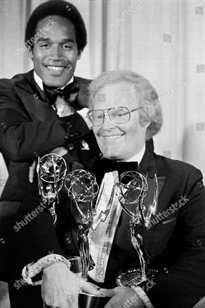 SIMPSON ARLEDGE Roone Arledge, executive producer for ABC-TV sports and news, holds an armful of Emmys at the 28th annual Emmy Awards show as footbal star O.J. Simpson looks on