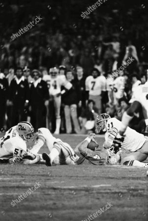 Clemson quarterback Steve Fuller is sacked and receives a chop to the chin as the Pittsburgh defense found their way through the Clemson line during the Gator Bowl in Jacksonville, Fla., . At left is Pittsburgh's Jeff Pelusi (51) and right is Bob Jury delivering the elbow. The action came during the second quarter of play
