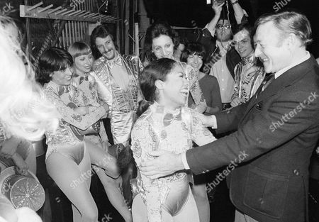 "Dancer Gene Kelly, right, embraces Baayork Lee, cast member of the musical ""A Chorus Line"" backstage at New York's Shubert Theater, . Miss Lee had been in the cast of the musical ""Flower Drum Song"" which Kelly had directed on Broadway. Other ""Chorus Line"" cast members look on"