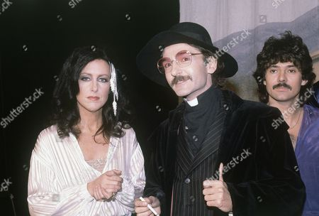 "Singer Grace Slick, left, and Mickey Taylor, right, of the Jefferson Starship are shown with comedian Don Novello of ""Saturday Night Live"" in character as Father Guido Sarducci"
