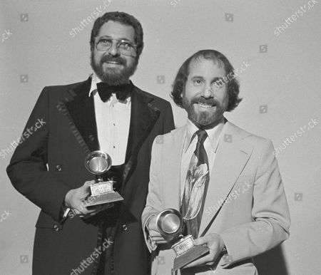 "Paul Simon, right, named best pop male vocalist of the year, holds the Grammy award given him in Hollywood by the National Academy of Recording Arts and Science, in Los Angeles. His ""Still Crazy After All These Years"" was named best album of 1975. At left is the album's co-producer, Phil Ramone"