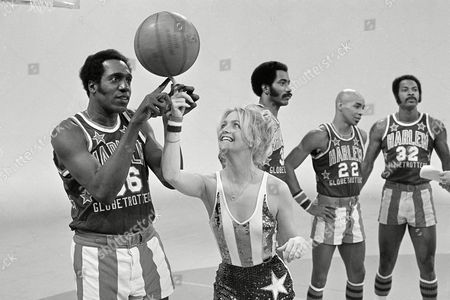 Actress Goldie Hawn has her finger guided to the basketball by Harlem Globetrotters' Meadowlark Lemon, during the taping of her CBS special in Burbank, Calif.,. In the background are teammates Curly Neal and Robert Paige, other player is unidentified