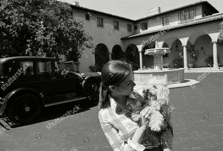"""Front of Harold Lloyd's home in Beverly Hills in May 1973 shows courtyard and fountain. The car at left is a 1924 Rolls Royce. Suzanne Lloyd Guasti, 21, granddaughter of Harold Lloyd, romps with her poodle, """"Corky"""