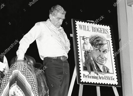 James Whitmore, the actor who has portrayed humorist Will Rogers in one-man shows since 1970, stands next to an enlargement of a commemorative stamp on the stage of Fords Theatre, Washington, D.C. The U.S. Postal Service will place the stamp on sale November 4 to honor Rogers 100th birthday