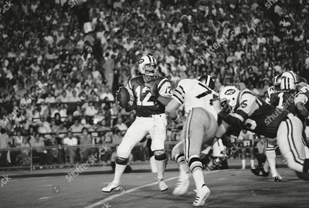 New York Jets' Joe Namath (12) gets set to launch a delivery to Rick Caster as New Orleans Saints Billy Newsome (78) puts on the pressure, . Jets blocking are Winston Hill (75) and Mike Adamle