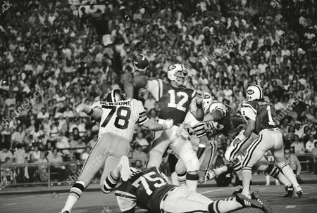 New York Jets' Joe Namath (12) gets set to launch a delivery to Rick Caster as New Orleans Saints' Billy Newsome (78) puts on the pressure, . Jets blocking are Winston Hill (75) and Mike Adamle