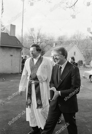 Pres. Jimmy Carter, right, carries a Bible as he walks alongside the Rev. Charles Shaffer at the Harriet Episcopal Church where he attended services, Catoctin Furnace, Md. Visible between and behind them is Ben Griffiths of Hawkinsville, Ga., father of Caron Carter