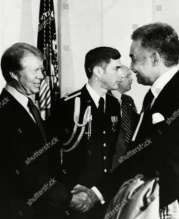 Pres. Jimmy Carter, left, greets Detroit Mayor Coleman Young, right, during a reception at the White House, Washington, D.C. It was one of a series of parties that Carter hosted during the day. The man at center is unidentified