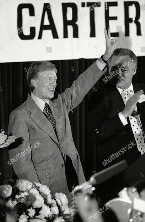 Jimmy Carter reacts to applause after his speech to the Democratic National Committee in Washington, . Carter said he was looking forward to 1980 but has not yet formally announced his candidacy. At right is Detroit Mayor Coleman Young