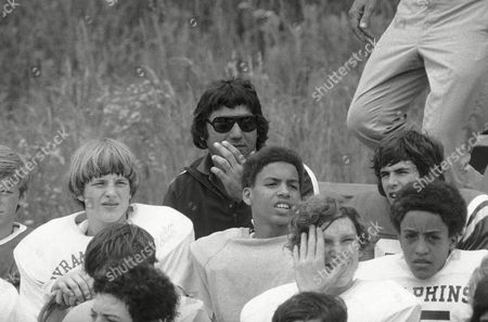 The face of New York Jets quarterback Joe Namath looms up behind aspiring gridders at instructional camp in Dudley,Mass. for kids 8-18 years old, . The camp is run by Namath and former teammate John Dockery, now a cornerback with the Pittsburgh Steelers