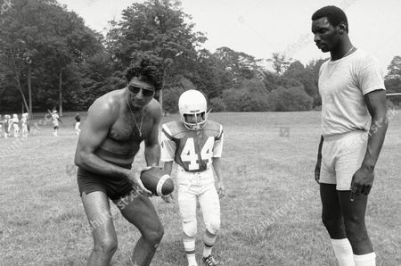 Doug Williams, right, the rookie quarterback who is due to report to Tampa Bay, and Joe Namath, left, show a youngster a move at the Joe Namath-John Dockery Football Camp at Hamden, Connecticut