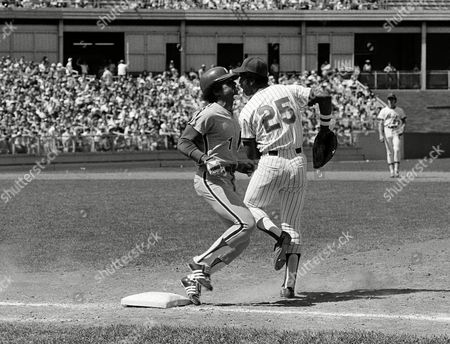 Willie Montanez (25), of the New York Mets, playing at first base, does a little side step to avoid Jose Cardenal of the Phillies during the fifth inning in New York, . The Mets made a comeback during the game after being down 5-0 in the first inning and they won, 6-5