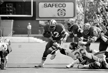 Mississippi State's Mike Lawrence, 26, grabs the leg of University of Washington's Ron Gipson, 42, after taking a handoff from Warren Moon, 1, during first half action in Seattle. Moving in to help protect Gipson is Washington's Phil Foreman