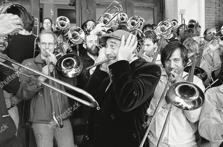 Conductor Mitch Millar holds his ears as music from 76 members of the International Trombone Association blasts out, in Boston, after their rehearsal as soloists in Sunday evening's Boston Pops concert. The trombonist range in age from thirteen to fifty