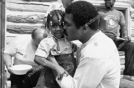 Muhammad Ali takes time out from training at Deer Lake, Penn. where he is preparing for his October 2 bout against Larry Holmes, to plant a kiss on cheek on Melissa Smith, . The three-year-old from Plainfield, New Jersey was among those watching the champ prepare for his Las Vegas comeback attempt