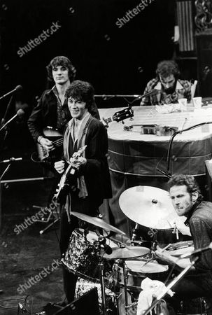 The Band take the stage for their final live performance before a crowd of 5,000 at Winterland Auditorium in San Francisco, . The Band consists of five members, Richard Manuel on piano, Levon Helm on drums, lead guitarist Robbie Robertson (smiling), bass guitarist Rick Danko, and organist Garth Hudson (not shown
