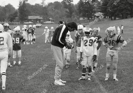 Joe Namath has his hold on the ball and the youngsters' attention as he teaches some of football's finer points at his instructional camp in Dudley, Mass., . Kids from 8-18 years of age go to the camp run by the New York Jets quarterback and his former teammate, John Dockery