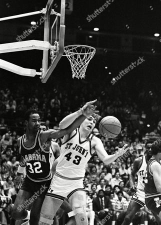 Stock Photo of Frank Gilroy, right, of St. John's University and Ken Johnson of the University of Alabama rub elbows as Johnson slaps a rebound out of Gilroy's arms in the second half of first round game, in the National Invitational Tournament at St. John's, New York