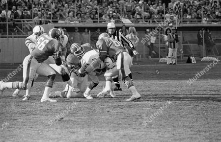 Stock Image of Baltimore quarterback Bert Jones (7) is sacked by Denver Broncos' Barney Chavous (79) and Rubin Carter (68) while Brison Manor (66) heads in for the kill during Denver's 27-13 victory in Denver