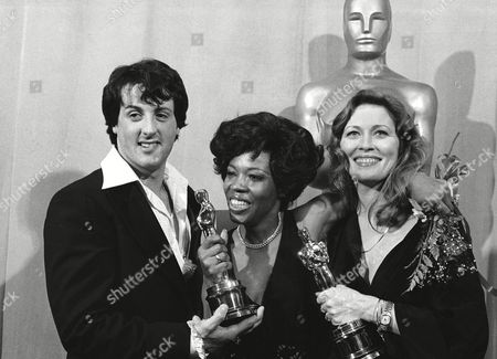 "Sylvester Stallone, left, star of ""Rocky,"" poses with Eletha Finch, widow of actor Peter Finch, and actress Faye Dunaway, at the Academy Awards in Los Angeles, . Mrs. Finch accepted the best-actor Oscar won by her late husband in ""Network."" Miss Dunaway was named best-actress for her performance in the same film. ""Rocky,"" written by Stallone, was named best picture"