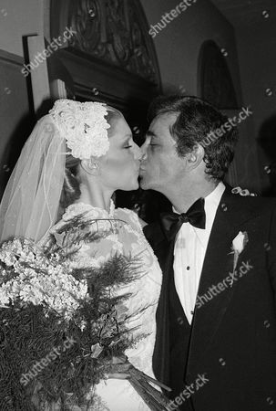 Actor Peter Falk kisses actress Shera Danese as they emerge from the Church of the Good Shephard shortly after their wedding ceremony in Los Angeles on . A black tie dinner and dance followed with celebrities such as John Cassavetes, Ben Gazzara, and Bob Dishy attending