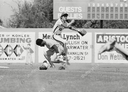 Philadelphia Phillies shot stop, Larry Bowa (10) gets bumped by Montreal Expo Jerry White as he completes the double play throw in the first inning of the exhibition game, Clearwater, Fla. White was forced at second when teammate Dave Cash grounded to second
