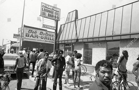 Bystanders mill around area near the Bob Bolton bar, background in Detroit, where according to police, Andrew Chinarian, who owns the bar, shot a teenager attempting to break into a car. In foreground and across parking lot from where shooting occurred is the Coleman Young Lounge and Bar-B-Q, formally owned by the Detroit Mayor Coleman Young