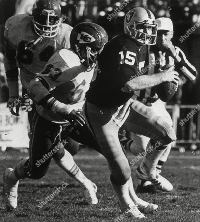 Raiders' quarterback Mike Rae (15), playing in place of resting Ken Stabler, twists away from Kansas City Chiefs linebacker Willie Lanier (63) in first half action at Oakland, Calif., . Behind Lanier is Chiefs' end Whitney Paul (64). Raiders squeezed by 21-20