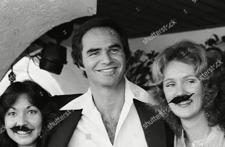 """Burt Reynolds, who recently shaved off his moustache of 11 years on Johnny Carson's """"Tonight Show,"""" gets a laugh when two guides at the Movieland Wax Museum in Buena Park showed up with these fake ones, . The guides are Jane Figueroa, left, and Judy Campbell"""