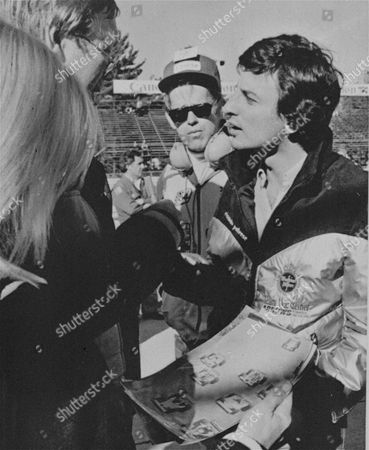Riccardo Patrese, right, tries to convince reporters, that he was not at fault in the crash in Monza, Italy, by showing photos, foreground, that he claims show that he was not at fault in the crash that killed Grand Prix driver Ronnie Peterson. Patrese later went to Elmira to seek a court injunction against the running of Sunday's Grand Prix because he has been barred from driving