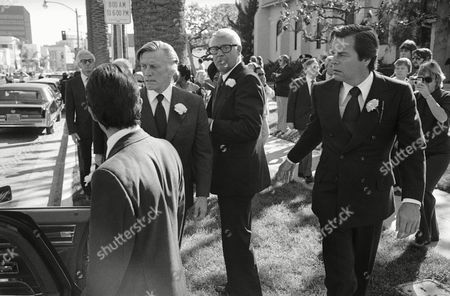 Stock Image of Actors Kirk Douglas, center left, Cary Grant, center, and Robert Wagner, right, stand outside the Church of the Good Shepherd in Beverly Hills, California, after funeral ceremonies for actress Rosalind Russell. All three were pallbearers