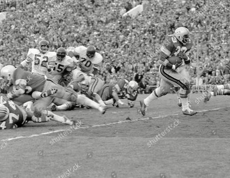 Pete Johnson, Ray Rodriguez, Charles Anthony, Art Riley Fullback Pete Johnson charges across the goal line from four yards out for his third touchdown in Ohio State's 42-21 rout of Southern California in the Rose Bowl game in Pasadena, California on . His teammates blew a hole in USC's line, stopping, among others, linebacker Ray Rodriguez (52), linebacker Charles Anthony (55), and tackle Art Riley (70