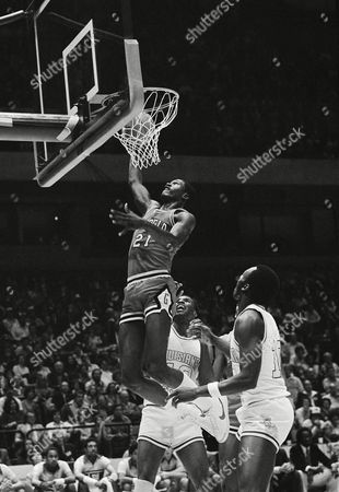 """Georgia's Dominique Wilkins (21) slams the ball through the net as he """"slam dunks"""" a score during SEC Basketball Tournament action against LSU in Birmingham, . LSU's Burand Macklin looks up at the score. Georgia upset LSU 68-60"""
