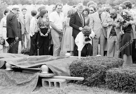 "Neysa Moskowitz Mrs. Neysa Moskowitz touches the coffin of her daughter Stacy at King Solomon cemetery in Clifton, N.J., watching at right, his hands clasped, is Jerome Moskowitz, the slain girl's father. At extreme right, in black dress is Ricki, 16, the Moskowitz only surviving child. State is the latest victim of New York's .44-caliber killer, who calls himself ""Son of Sam"