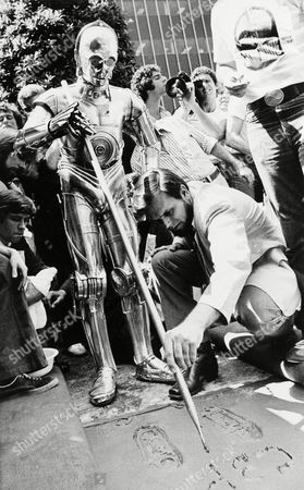 "Joining movie stars of the past and present, C-3PO, one of the famous robots from the 20th Century-Fox film ""Star Wars,"" places his foot prints in the cement in front of Mann's Chinese Theater in Los Angeles, Calif., . Assisted by studio personnel, C-3PO signs his name and thereby joins such stars as Greta Garbo, Clark Gable and Barbra Streisand"