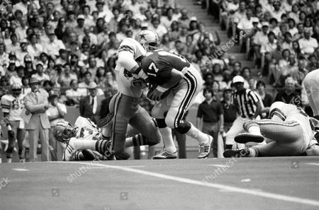 Dallas Cowboys' linebacker Thomas Henderson grabs St. Louis quarterback Jim Hart (17) and twists him to the turf far a loss in the second half of Sunday's game at Texas stadium on in Irving. This was one of three sacks for Henderson, who combined with the rest of the Cowboys' defense, sacked hart seven times. The Cowboys won the game, 22-13