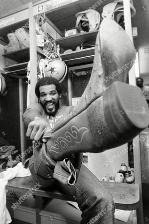 "Dallas Cowboys strong side linebacker Thomas ""Hollywood"" Henderson pulls on a new pair of cowboy boots after practice on in Dallas. Henderson who is never at a loss for words says he will use the new boots to kick the Pittsburg Steelers out of Super Bowl XIII"
