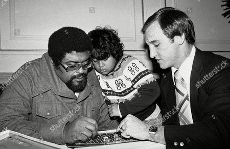 """Rosey Grier, Spike Grier, Roosevelt Kennedy Grier, Steve Grogan Rosey Grier, who was once notorious as the New York Giants crusher who just grabbed an armful of enemy players instead of making tackles, looks over a game at the Pre-American Toy Fair in New York City, . Looking on at center is Grier's son, Spike, and Steve Grogan of the New England Patriots. Grogan is promoting the strategy football game. Grier says he is now involved in gentler pursuits that start with children. he says he is """"hepped on kids"""" because they are our only hope"""