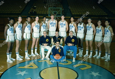 The UCLA basketball team is seen in 1972, standing, from left to right: Tommy Curtis, Greg Lee, Larry Hollyfield, Jon Chapman, Keith Wilkes, Bill Walton, Swen Nater, Vince Carson, Larry Farmer, Gary Franklin, Andy Hill, and Henry Bibby. The coaches seated in front of them are unidentified